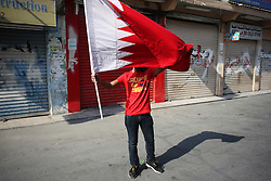 Protesters carry the Bahraini flag in the streets, and often must deal with tear gas, rubber bullets and bird shot