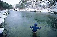 A young man fly fishes during a snowy fall day on the Teton River, Idaho.