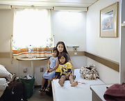 Mathelda Liyanti with her children Vasco and Caessaria in their first class cabin of KM Bukit Siguntang. She came from Toraja, a landlocked and mountainious region in South Sulawesi, to visit her husband who work in Maumere in the island of Flores. She bought Pelni's tickets from the Port of Makassar since there is no direct flight available. The journey took 16 hours.<br /> <br /> Indonesia&rsquo;s Pelni is the last great true passenger liners company in the world. It is the only company of its size that still serves scheduled vessels transporting people across various destination. In a far-flung archipelago nation, where many of the islands have no airport and most of its area made up of water, it is one important mean of transportation&mdash;and simply one of the best way to travel. One of Pelni's furthest regular route starts from Surabaya in East Java and ends in Papuan city of Merauke, basically the eastern end of Indonesia. The round trip voyage takes one month, passing more than two dozen ports and covering a distance of more than 8,000 kilometers.