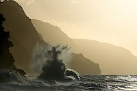 Waves break against the beautiful Napali coastline near sunset.  This wave formed the shape of a crucifix, Kauai, Hawaii, USA.