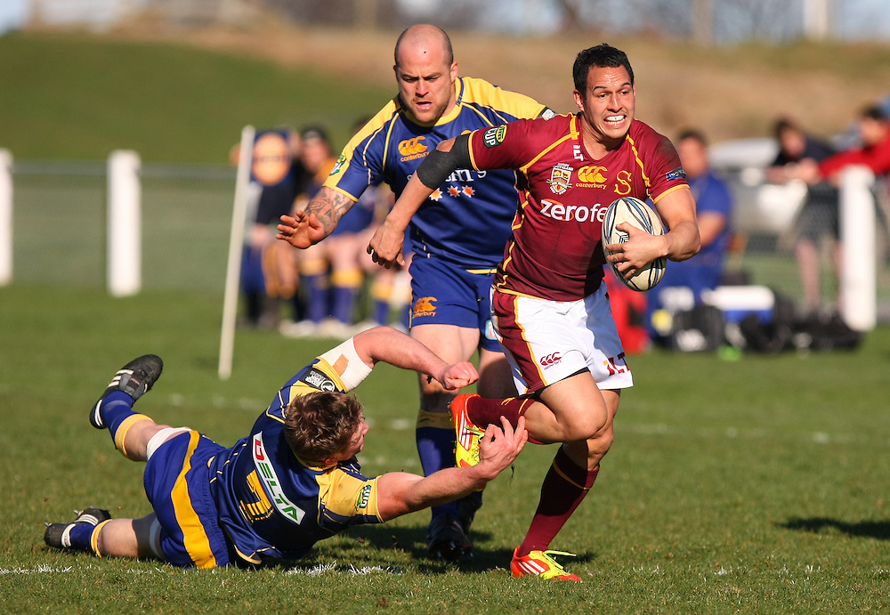 Southlands' Tim Cornforth, right, slips through the tackle of  Otagos' Gareth Evans, left, in the ITM rugby preseason match, Balclutha, New Zealand, Friday, August 17, 2012. Credit:SNPA / Dianne Manson