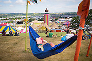 The sun continues to shine on the second day of Glastonbury Festival after it opened it's gates yesterday for the early arrivals. Approximately 170,000 revellers are set to turn up to the festival which is hosting a number of headliners including Kanye West and Alt J. <br /> Pictured: A festival goer enjoys a nap in the sunshine overlooking Glastonbury Festival on day two.