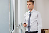 Thoughtful businessman holding smart phone while looking through window at home