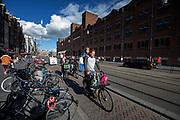 Een man fietst met zijn kind staand op de bagagedrager over het Damrak in Amsterdam.<br /> <br /> A man cycles with his child standing on the luggage carrier at the Damrak in Amster.dam