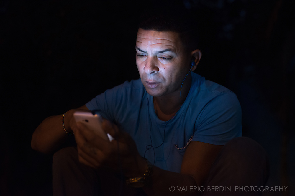 A man lit up by his  smartphone in Parque Fe del Valle in Havana de Cuba, on the afternoon of 29 December 2015. Cuban parks, usually poorly illuminated at night, glow by the flickering lights of several electronic device. This man was aware I was photographying, but he was not bothered and continued using the phone. This photo was not staged.