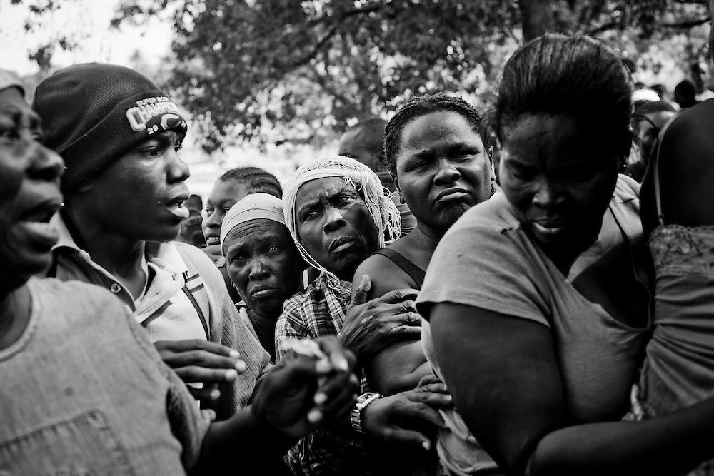 People wait in line for food distributed by USAID in a camp for those displaced by the recent earthquake in Petionville, outside Port-au-Prince, Haiti.