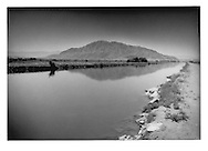 The All-American Canal parallels the US/Mexican border, outside Calexico, California, USA.  The mountain in the background which the canal appears to approach, sits south of the border.  The All-American Canal, which went into operation in 1944, provides potable water for 9 cities and irrigates over 530,000 acres (2,000 km²) of agricutlural land.   It is the largest irrigation canal in the world, carrying up to 26,155 cubic feet per second of water.  Seepage from this canal, which feeds the water table to Mexicali, adjacent and south of the border, will be decreased if the US carries through with construction of a more efficient canal.
