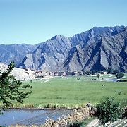 Late Summer? 1965<br /> Green fields. Village nestled at foot of barren mountain slope.
