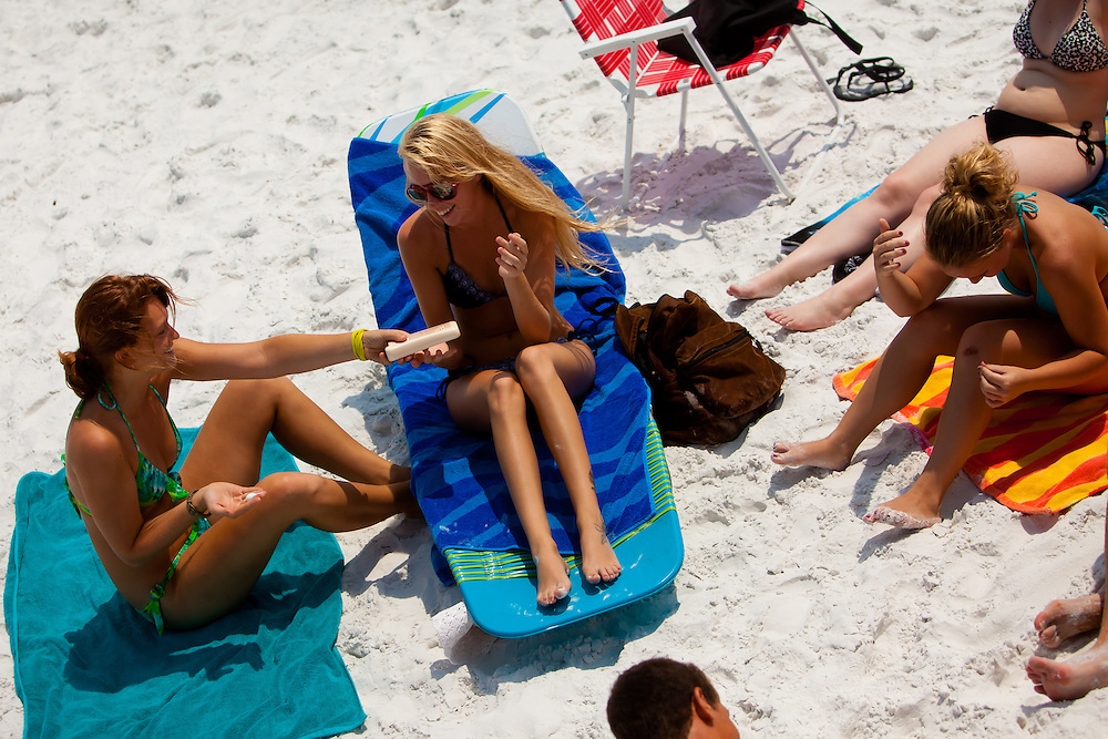 SARASOTA, FL -- June 14, 2011 --  Kali Gough, 17, left, and Allie Harris, 18, center, both of Sarasota, apply sunscreen as they prepare to lay out at Siesta Public Beach in Sarasota, Fla., on Tuesday, June 14, 2011.
