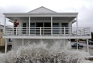 A man makes pictures as the surf from the Atlantic Ocean pounds into the barricade in front of his home  September 18, 2003 in Ventnor, New Jersey. Hurricane Isabel brought high winds and heavy surf to the New Jersey coast. (Photo by William Thomas Cain/photodx.com)