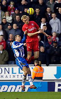 Photo: Jed Wee.<br />Wigan Athletic v Liverpool. The Barclays Premiership. 11/02/2006.<br />Liverpool's Sami Hyypia (R) jumps to win the ball from Wigan's Paul Scharner.