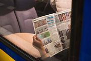 Een treinpassagier leest de Metro-krant