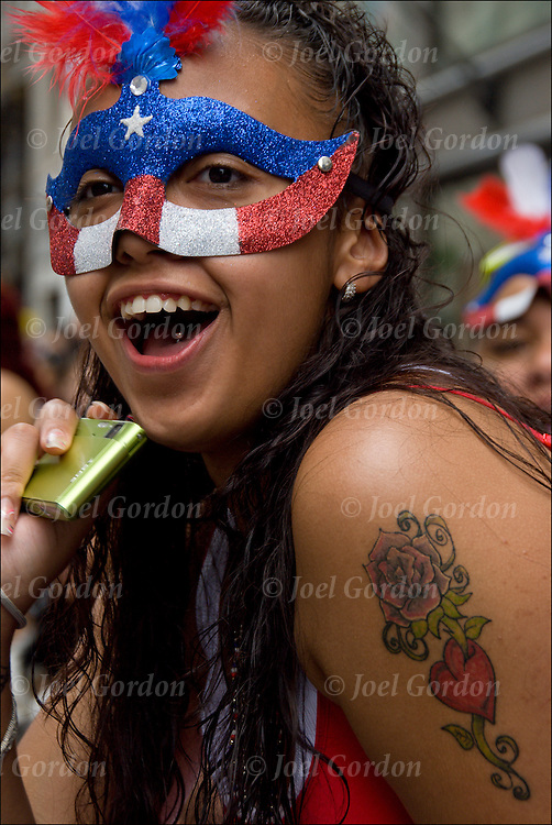 Close up of young female wearing mask with colors of Puerto Rican Flag, holding a point and shot camera, rose tattoo on arm and tongue piercing.  She is just one of the faces in the crowd at the 2009 Annual National Puerto Rican Day Parade is a celebration for the Puerto Rican American community in the Northeast United States to show their ethnic pride.