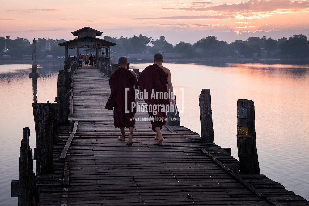 Two monks walk across the wooden U Bein's Bridge near Amapura in Mandalay.