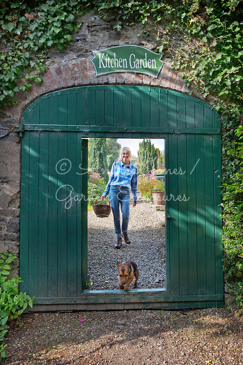 Catherine FitzGerald with Sooty at the gates to the Kitchen Garden at Glin Castle, Ireland