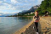Child (5 years old) walking along beach in late afternoon sun, with the Biokovo National Park, part of the Dinaric Alps, in the background. Makarska, Croatia