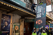 Theatre hoardings for the West End production of comedian Bill Bailey's Christmas performances, 'Larks in Transit' are manhandled up for mounting outside Wyndham's Theatre, on 3rd December 2018, in London, UK