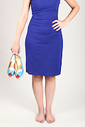Woman in blue dress holds her high heel shoes