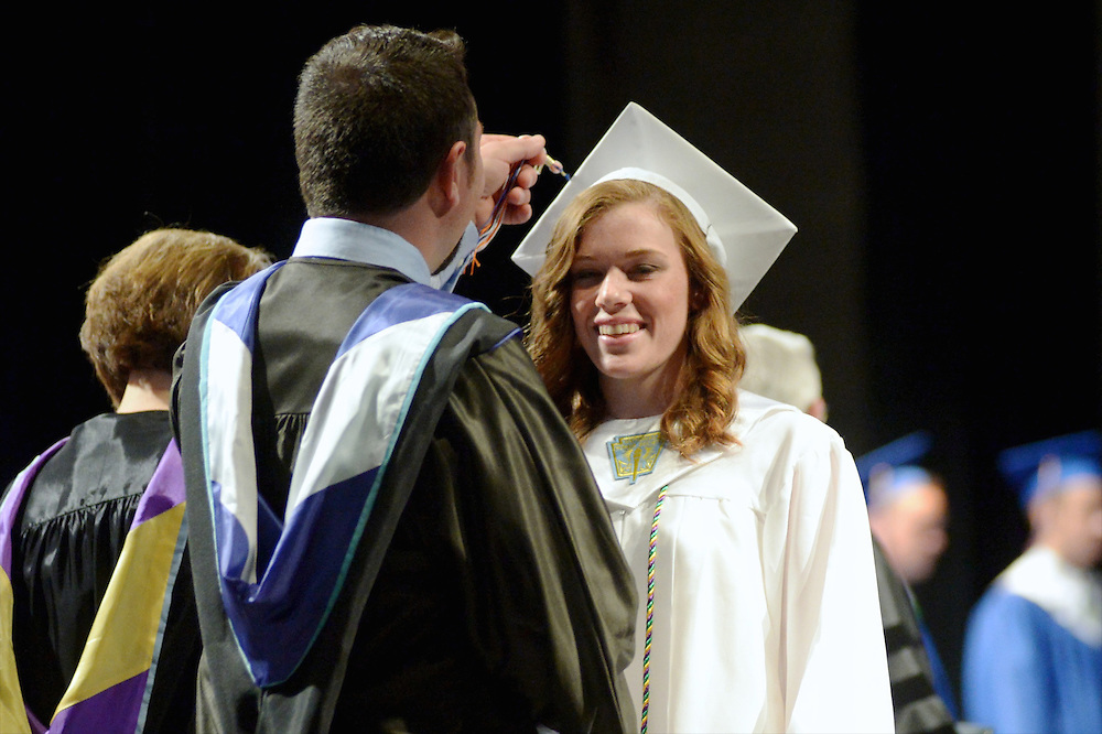 Class of 2014 advisor Michael Cronmiller (left) flips the tassel for graduate Erica Eck during the presentation of diplomas during the June 21, 2014 commencement ceremonies in Livonia.