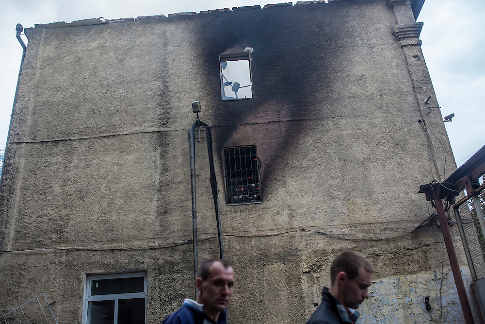 MARIUPOL, UKRAINE - MAY 9: Men walk past a police station which was attacked and burned on May 9, 2014 in Mariupol, Ukraine. Witnesses said that Ukrainian National Guard soldiers opened fire on police officers who refused orders to disperse a pro-Russia rally. (Photo by Brendan Hoffman/Getty Images) *** Local Caption ***