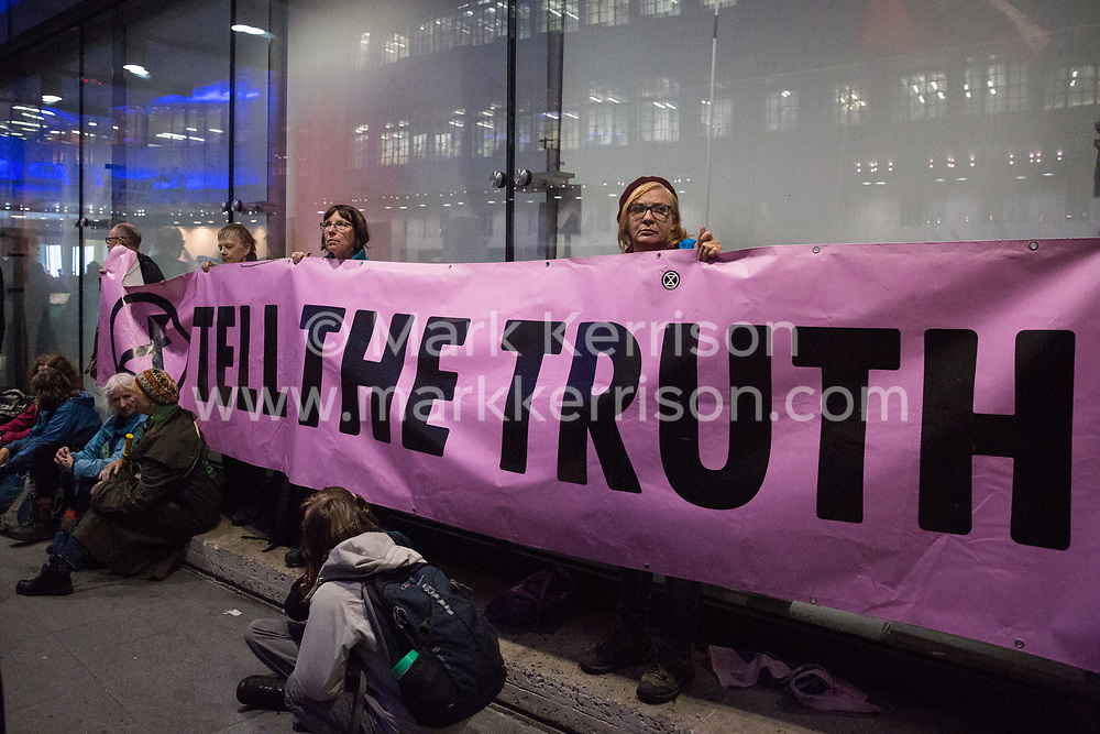 London, UK. 11 October, 2019. Climate activists from Extinction Rebellion block the main entrance to the BBC's New Broadcasting House on the evening of the fifth day of International Rebellion protests. They were demanding that the broadcaster 'tell the truth' regarding the climate emergency.