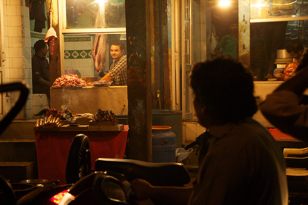 A butcher is contemplating Old Dehi nightlife from his shop.