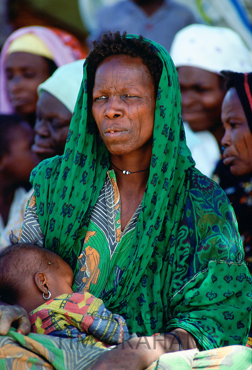 Woman with tribal markings on her face holding her baby close, Northern Nigeria