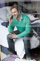 Man using mobile phone sitting on bed view through window