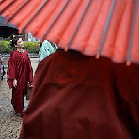 Asia, Tokyo, Japan, Japanese woman wearing kimono holding umbrella during spring rain
