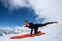 A female alpine climber practices yoga postures at the snowy ridge of iconic Aiguille du Midi, Chamonix, France on May 29 2012. This amazing location offers astounding views on the summit of Mont Blanc.