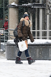 © Licensed to London News Pictures. 28/02/2018. London, UK. A woman walks around the City of London as heavy snowfall hits central London at lunchtime. The cold spell named The Beast From The East is due to last a few days. Photo credit: Ray Tang/LNP