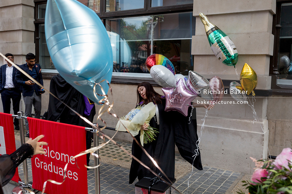 Hillary Chung, a 21 year-old Law graduate from Hong Kong, celebrates her graduation with a 2:1 degree outside the London School of Economics (LSE) after her graduation ceremony, on 22nd July 2019, in London, England.