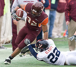 Virginia Tech running back Darren Evans (32) sheds a tackle from Virginia safety Byron Glaspy (22) along the sidelines.  The Virginia Tech Hokies defeated the Virginia Cavaliers 17-14 in NCAA football at Lane Stadium on the campus of Virginia Tech in Blacksburg, VA on November 29, 2008.