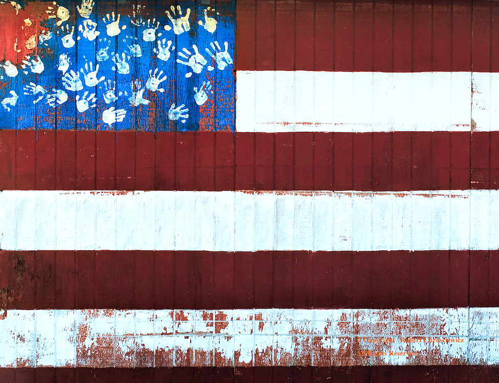 Faded Dream: This artistic representation of a weathered American flag was found on a work shed; it uses children's hand prints in place of the stars and can be viewed as a visual metaphor; of the worn aspirations and dreams of its country and youth, in Aberdeen Washington, United States of America.
