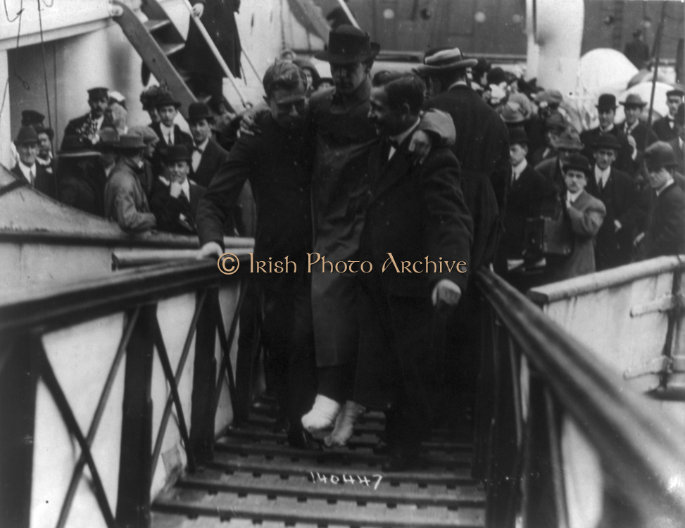 Loss of White Star Line's Olympic-class vessel RMS Titanic which struck an iceberg on 12 April 1912 on her maiden voyage. Surviving wireless operator, Harold Bride, feet bandaged, being carried up gangway, New York. Disaster