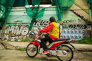 16 OCTOBER 2012 - BANGKOK, THAILAND: A motorcycle taxi parked next to an abandoned building on Phetchaburi Rd in central Bangkok, Thailand. The building used to be an optician's shop with residences above the ground floor shop. The global economic slowdown had little visible effect in Bangkok. Construction projects dot the city of 12 million and development continues unabated.    PHOTO BY JACK KURTZ