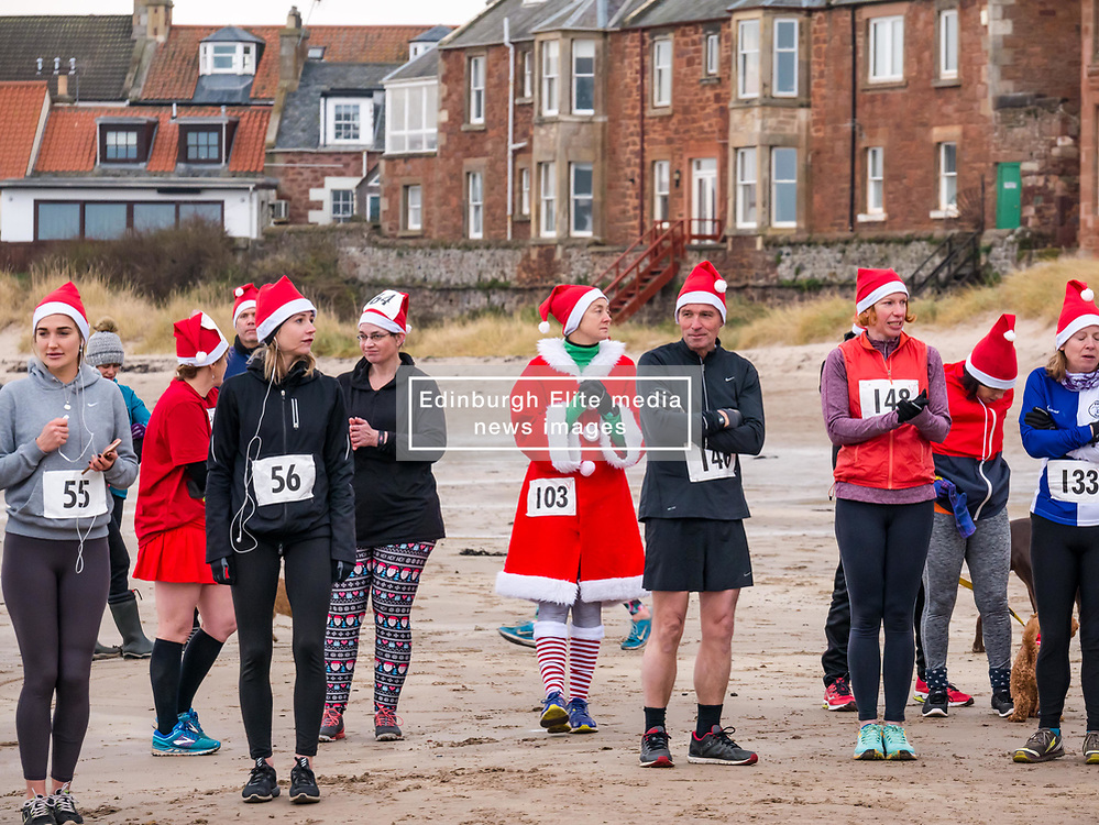 Pictured: Santa Beach Run on the scenic East Lothian coast. This new event is aimed at athletes, casual runners and families. It is hosted by Project Trust with proceeds enabling local school leavers to spend a year volunteering in India/Honduras to teach at a school with few teaching materials.  The adults prepare for the 5km and 10km races. 15 December 2018  <br /> <br /> Sally Anderson | EdinburghElitemedia.co.uk