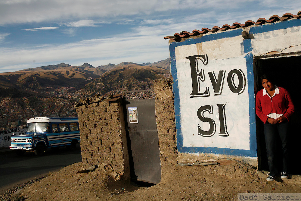 "Backdropped by the city of La Paz, Giovana, a young waitress and supporter of Bolivian president Evo Morales stands by the door of his relative's bar in the city's outskirts Friday, Aug. 1, 2008.Bolivians will hold a national recall vote on August 10 that could either grant greater support to Morales, his vice president and eight state governors or force them to step down. The grafitti in the wall reads ""Evo Yes"". (AP Photo/Dado Galdieri)"