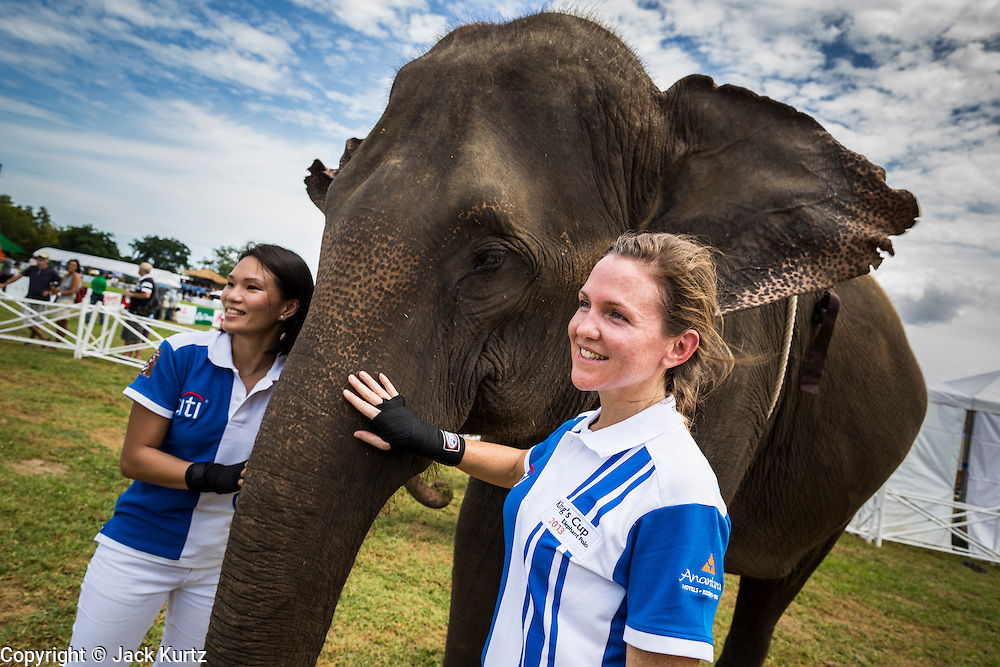 "28 AUGUST 2013 - HUA HIN, PRACHUAP KHIRI KHAN, THAILAND: WANVISA KOMIDR and AMANDA SILLARS of the Citibank team, walks past an elephant at the King's Cup Elephant Polo Tournament in Hua Hin, Thailand. The tournament's primary sponsor in Anantara Resorts and the tournament is hosted by Anantara Hua Hin. This is the 12th year for the King's Cup Elephant Polo Tournament. The sport of elephant polo started in Nepal in 1982. Proceeds from the King's Cup tournament goes to help rehabilitate elephants rescued from abuse. Each team has three players and three elephants. Matches take place on a pitch (field) 80 meters by 48 meters using standard polo balls. The game is divided into two 7 minute ""chukkas"" or halves. There are 16 teams in this year's tournament, including one team of transgendered ""ladyboys.""    PHOTO BY JACK KURTZ"