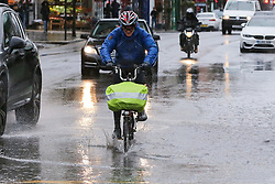© Licensed to London News Pictures. 12/03/2019. London, UK. A cyclist rides through a flood on Green Lanes, Haringey in North London after a heavy downpour. Photo credit: Dinendra Haria/LNP