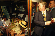 A group of young men are standing in a train corridor admiring some attractive young ladies through the open door of a railway compartment. They are all on their way from London's Waterloo mainline station to Ascot in Berkshire for Ladies Day during the Royal Ascot racing week. In the foreground, a lad wearing a dark suit and yellow tie tugs on his shirt sleeve in a confident and assertive manner before approaching the girls to say hello. He and another man are looking amorously down towards the seated females who are dressed in summer skirts and tops, in readiness for a warm day at the races. Royal Ascot is held every June and is one of the main dates on the sporting calendar and social season.