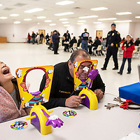 """Amanda Brown, 12, and Tomas Archuleta, a sergeant with the Cibola County Sheriff's office play Pie Face Game Wednesday Dec. 19 at the childrens carnival following """"Shop with a Cop"""" in Grants."""