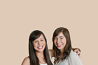 Portrait of young female friends over colored background