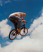 Teenager doing a trick on his BMX in the air