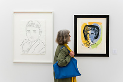 "© Licensed to London News Pictures. 17/05/2019. LONDON, UK. A visitor views ""Jacques Bellini"", 1983 (L), by Andy Warhol (GBP57,000) and ""Rimbaud"", 1948 (R), by Fernand Leger (GBP68,000) at the Draw Art Fair London, the first fair in the UK dedicated to modern and contemporary drawing.  58 international galleries have juxtaposed drawings with related paintings, sculptures, photos or videos, in a ratio of approximately 70% to 30%, using drawing as the core concept.  The inaugural show is open to the public 17 to 19 May 2019 at the Saatchi Gallery in Chelsea.  Photo credit: Stephen Chung/LNP"