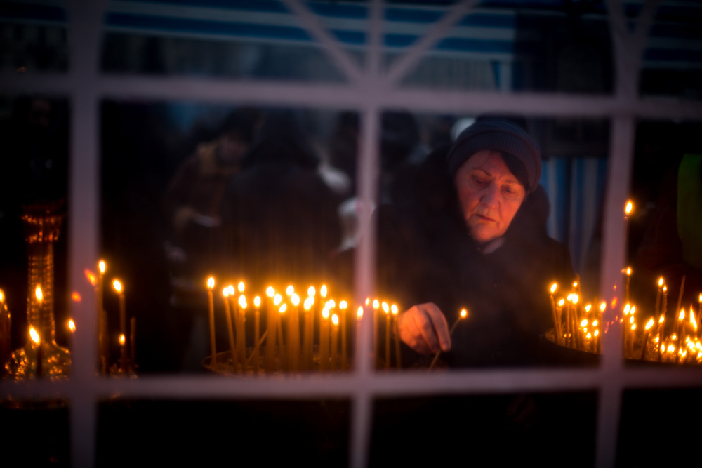 A woman lights up a candle, in an orthodox church tent, on the Independance Square, in Kiev.