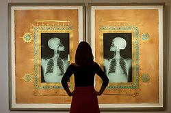 "© Licensed to London News Pictures. 13/10/2016. London, UK. A Sotheby's staff member views ""Illumination XIX & XX, 2005"" by Ahmed Mater (est. GBP 18-25k) at the preview of Sotheby's Art of the Middle East and India exhibition, which presents artworks to be sold in New Bond Street in four sales in October. Photo credit : Stephen Chung/LNP"