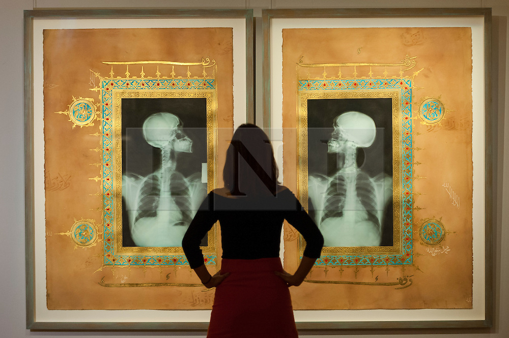 """© Licensed to London News Pictures. 13/10/2016. London, UK. A Sotheby's staff member views """"Illumination XIX & XX, 2005"""" by Ahmed Mater (est. GBP 18-25k) at the preview of Sotheby's Art of the Middle East and India exhibition, which presents artworks to be sold in New Bond Street in four sales in October. Photo credit : Stephen Chung/LNP"""