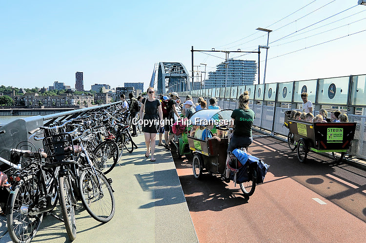Nederland, Nijmegen, 19-6-2017Nu de Waaloevers en de Spiegelwaal intensief gebruikt worden als recreatiegebied, vooral met warm weer, is het soms een chaos van fietsen en badgasten op de snelbinder, de fietsbrug naar Lent. Fietsbrug, de snelbinder, die aan de spoorbrug is gehangen, en de verbinding vormt tussen de Waalsprong, nieuwe vinexwijken in oosterhout en Lent, en het centraal station. Hij is onderdeel van de snelfietsroute naar Arnhem.Foto: Flip Franssen