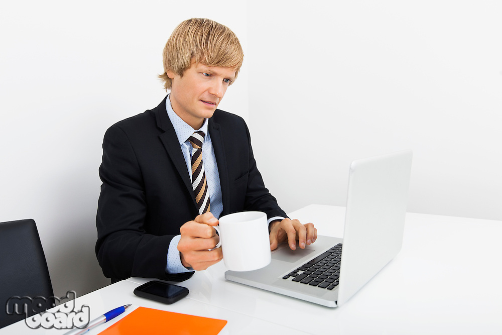 Businessman holding coffee cup while using laptop at desk in office
